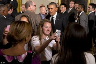 Ecstatic: Girls from the Stone Ridge School in Bethesda, Maryland soccer teams take selfies with President Barack Obama in the background after an event in the East Room of the White House where the president honored the 2013 Major League Soccer champions, Sporting Kansas City