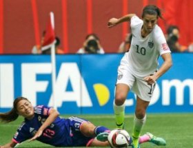 Japan's Rumi Utsugi, left, goes down as United States' Carli Lloyd moves with the ball during the second half of the FIFA Women's World Cup soccer championship in Vancouver, British Columbia, Canada, Sunday, July 5, 2015.